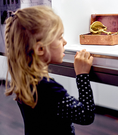 Mädchen schaut auf altes Werkzeug